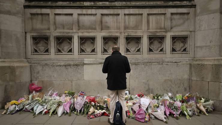 Ein Mann trauert vor den Blumengaben beim Parlamentsgebäude.
