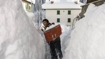 Ein Bub schaufelt Schnee im Dorf Bedretto im Tessin