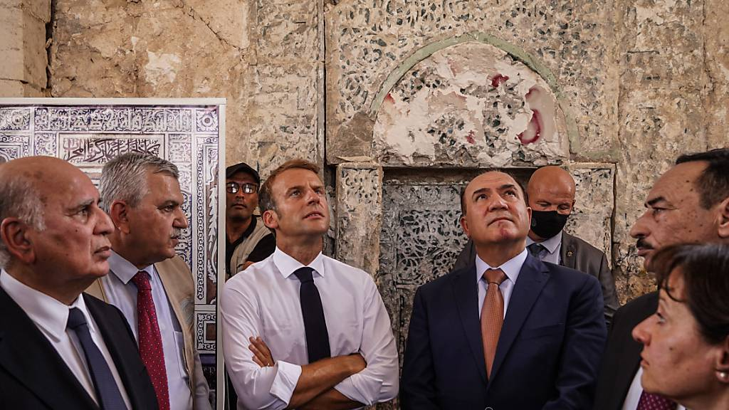 Emmanuel Macron (M), Präsident von Frankreich, besucht die Al-Nuri-Moschee in Mossul. Dabei sagt er der dortigen christlichen Minderheit Frankreichs Unterstützung zu. Foto: Ismael Adnan/dpa