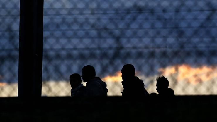 Jede Nacht versuchen hunderte Flüchtlinge durch den Eurotunnel von Frankreich nach Grossbritannien zu gelangen: Silhouetten von Migranten bei Calais, aufgenommen am Mittwochabend.