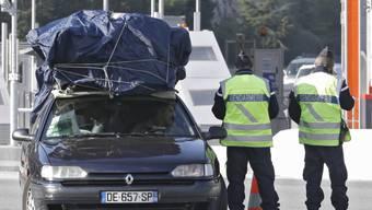 Französische Polizisten kontrollieren ein Auto an der Grenze zu Italien in La Turbie. (Archivbild)