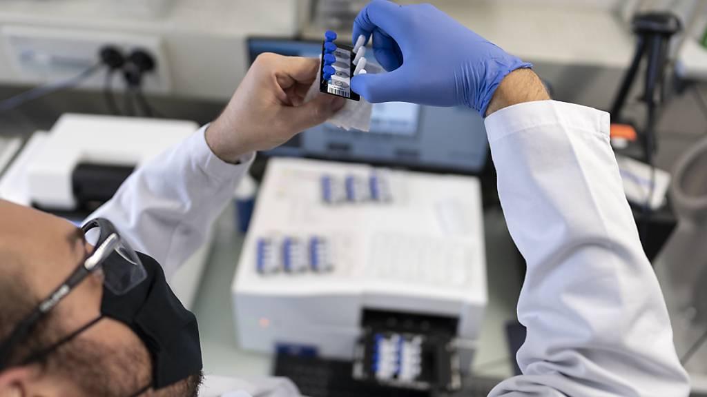 Dem Bundesamt für Gesundheit wurden am Dienstag 3150 neue Coronavirus-Ansteckungen innert 24 Stunden gemeldet. Ein Mitarbeiter des Wasserforschungsinstituts Eawag in Dübendorf bereitet Abwasserproben vor, um diese in einem digitalen PCR-Gerät auf Spuren des Coronavirus zu untersuchen. (Archivbild)