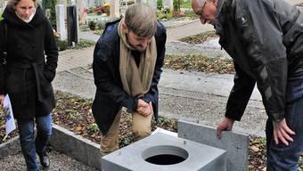 Da kommt die Asche hinein: Pfarrerin Kathrin Remund-Gugger, Bestattungsamtsleiter René Sandmeier und Friedhofgärtner Rudolf Zogg (v.l.) beim Einfüllwürfel aus Granit, der für die nächsten paar Jahre auf der ersten von fünf Gruften platziert ist.