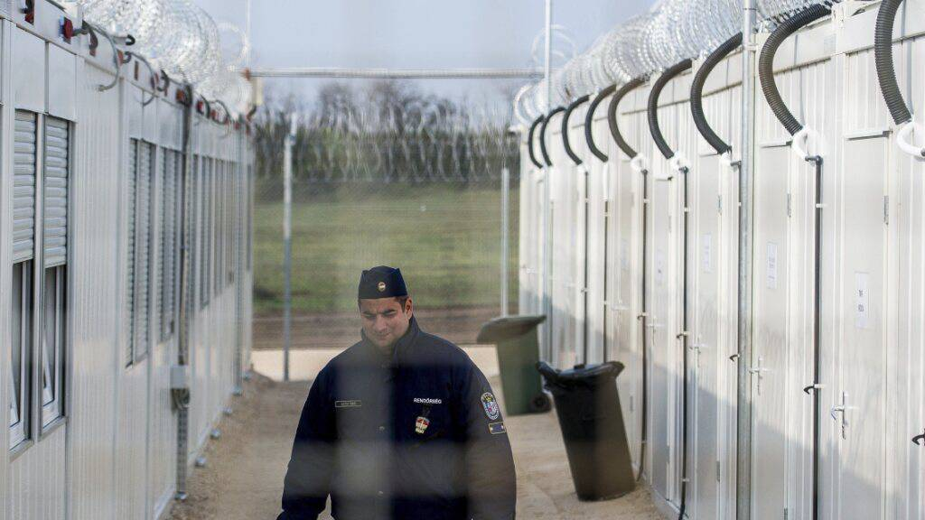 ARCHIV - Ein ungarischer Polizist patrouilliert durch das ein Internierungslager für Asylsuchende an der Grenze zu Serbien. Foto: Sandor Ujvari/MTI/AP/dpa