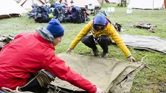 Zelt aufbauen, Zelt abbauen, und dazwischen viel erleben: Zwei Pfadfinder legen während eines Pfingstlagers in Kandersteg BE Zeltblachen übereinander. (Archiv)