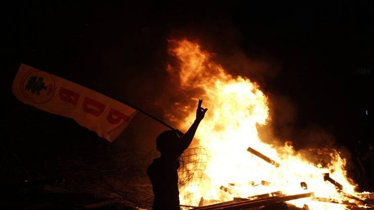 Demonstrant macht das Victory-Zeichen, als er vor einer brennenden Barrikade vorbeigeht