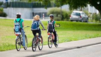 Drei Schülerinen pedalen auf dem Trottoir.
