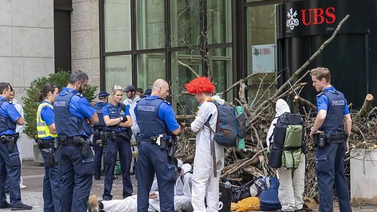 Polizisten räumten am Montag die Blockade der Aktivisten einer Gruppe namens «Collective Climate Justice» vor dem UBS-Bürogebäude am Aeschenplatz in Basel. Im Hintergrund eine Holzbeige, die an Schwemmholz erinnert, als Sperre vor der Türe.