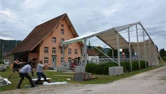 Mit vereinten Kräften wird die Blache über die vor dem Adam-Zelter-Haus aufgebaute Zuschauertribüne gezogen.