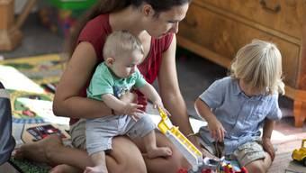 Eine Mutter spielt mit ihren beiden Kindern (Symbolbild)