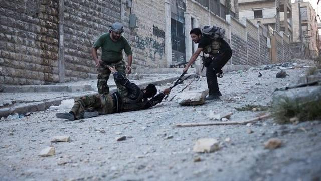 Syrische Rebellen mit einem verletzten Kameraden in Aleppo