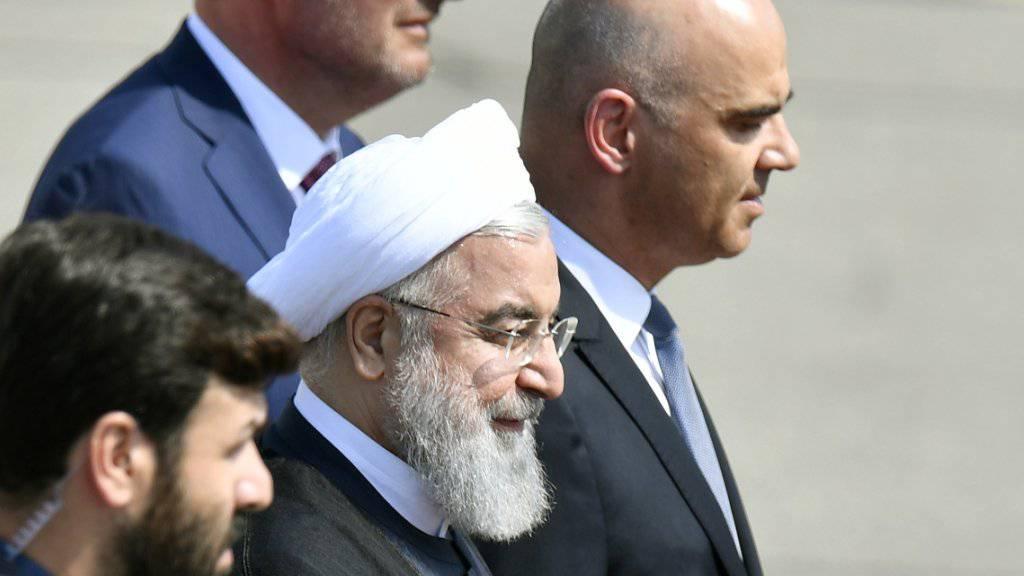 Der iranische Präsident Hassan Ruhani (Mitte, mit Kopfbedeckung) nach seiner Begrüssung durch Bundespräsident Alain Berset (rechts) auf dem Flughafen Zürich-Kloten.