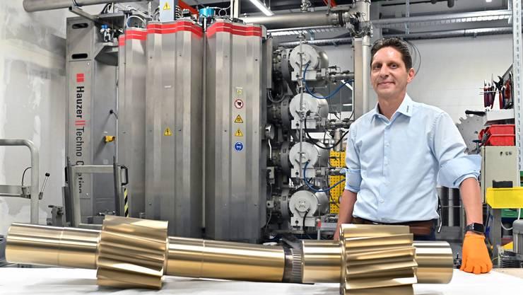 Geschäftsführer Robert Jäggi arbeitet seit 21 Jahren bei der Ionbond AG. Die goldenen Maschinenkomponenten wurden gerade beschichtet.