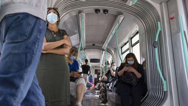 Passagiere mit Masken in einem Tram in Genf - demnächst müssen sie sogar im Auto getragen werden.