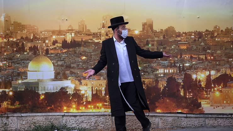 dpatopbilder - Ein ultraorthodoxer jüdischer Mann streitet sich mit einem Polizeibeamten, als er daran gehindert wird, eine Straße zu überqueren. Ein hauptsächlich ultraorthodoxes jüdisches Viertel ist aufgrund eines Coronavirus-Ausbruchs abgeriegelt worden. Foto: Oded Balilty/AP/dpa