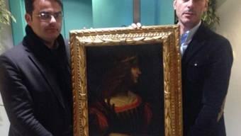 Zwei Tessiner Beamte zeigen das beschlagnahmte Bild (Polizeibild)