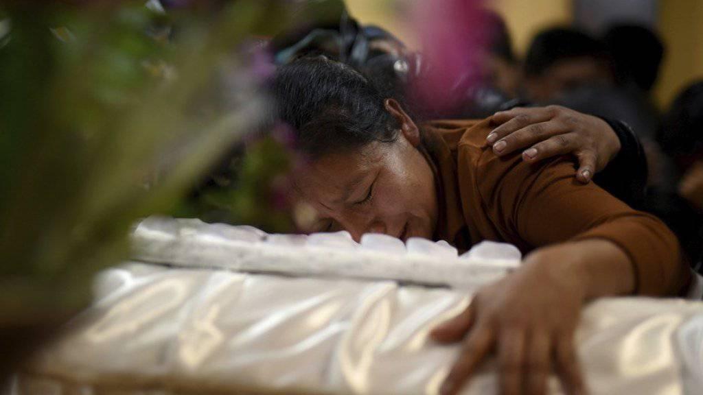 Eine Frau trauert während eines Trauergottesdienstes am Sarg ihres beim Brand im Heim in der Ortschaft San José Pinula nahe Guatemala-Stadt gestorbenen Kindes.
