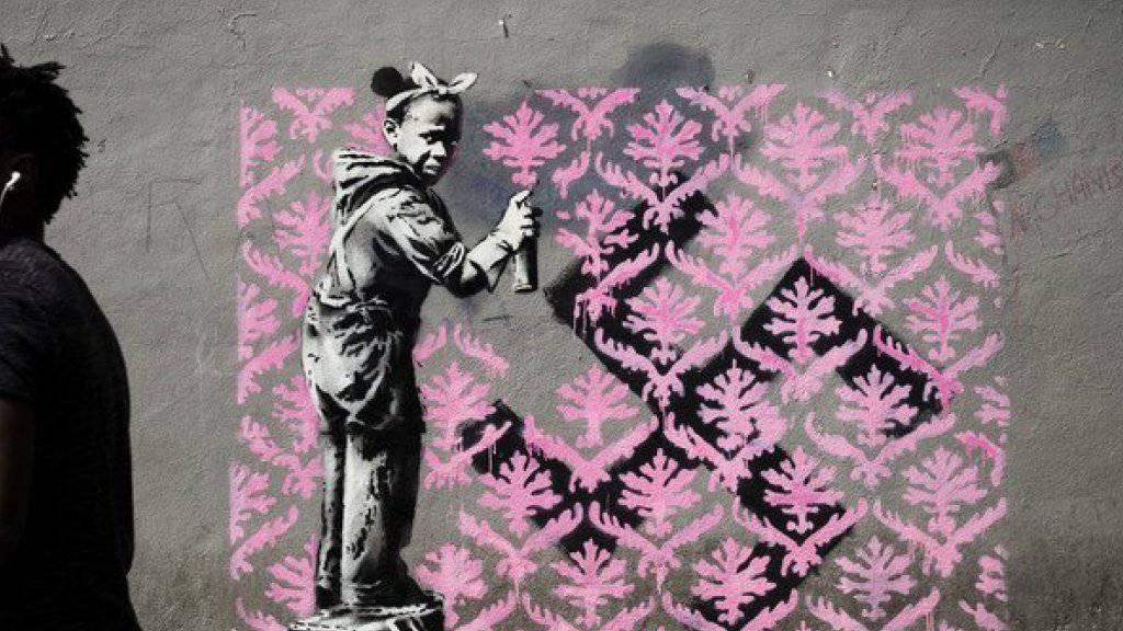 Auf Twitter wird gejubelt: Banksy ist zum ersten Mal in Paris! Bisher sind in der französischen Hauptstadt sechs mutmassliche Motive des Inkognito-Künstlers aufgetaucht. Hier ein Flüchtlingsmädchen, das ein Hakenkreuz mit einem rosa Blumenmuster übersprayt. (Twitter)