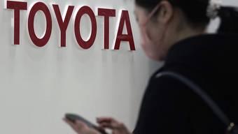 Die Schwäche der japanischen Währung war für den Autobauer Toyota ein Vorteil: eine Frau vor einem Logo des Unternehmens in Tokyo (Bild vom 30. Januar).