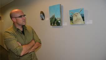 Philipp Koller betrachtet seine Werke mit den vermenschlichten Tieren in einer Alpenlandschaft.