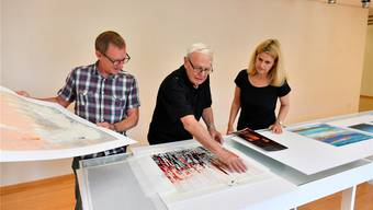 Toni Bieli zeigt Heinz Westreicher und Eva Inversini eines seiner Werke aus jüngster Zeit, das zu seinen Lieblingsbildern gehört.