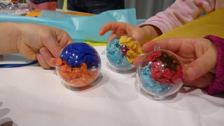 Kinder präsentieren ihre selber gebastelten Weihnachtskugeln