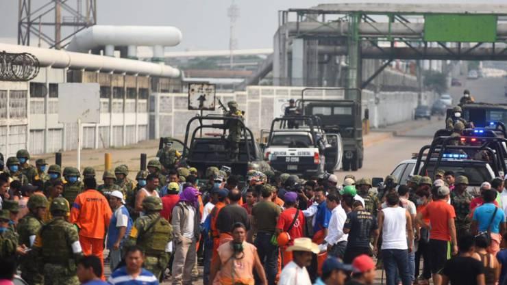 Angestellte der Raffinerie in Coatzacoalcos versammeln sich beim Zugang zum Werk. Nach jüngsten Angaben gab es 24 Tote bei der Explosion.