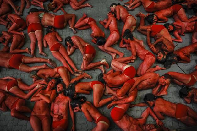 Die Aktivisten sind fast nackt, nur mit brauner, schwarzer und roter Farbe bemalt.
