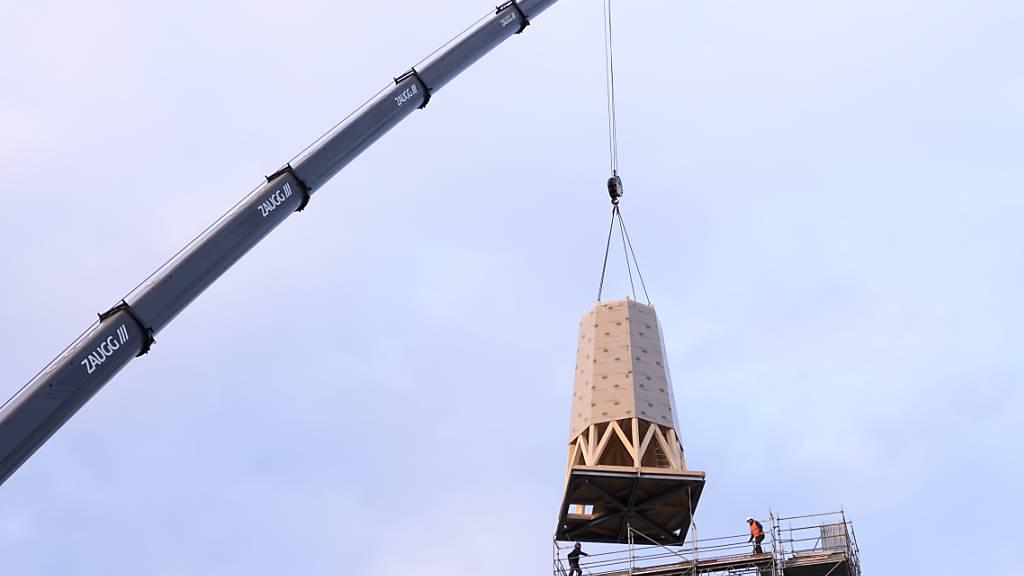 Der erste Teil der Turmspitze wird mit einem Autokran auf den Kirchturm in Herzogenbuchsee montiert. Der Kirchturm war an Heiligabend 2019 durch einen Brand zerstört worden.
