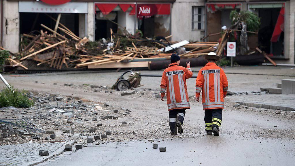 Hochwasser in Niederbayern: Zwei Feuerwehrmänner spazieren am Donnerstag durch die vom Unwetter verwüsteten Strassen von Simbach.