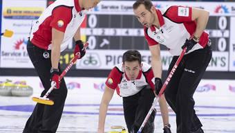 Schweizer Teamwork in Kanada: Peter De Cruz bei der Steinabgabe, Valentin Tanner (links) und Sven Michel in Wischbereitschaft