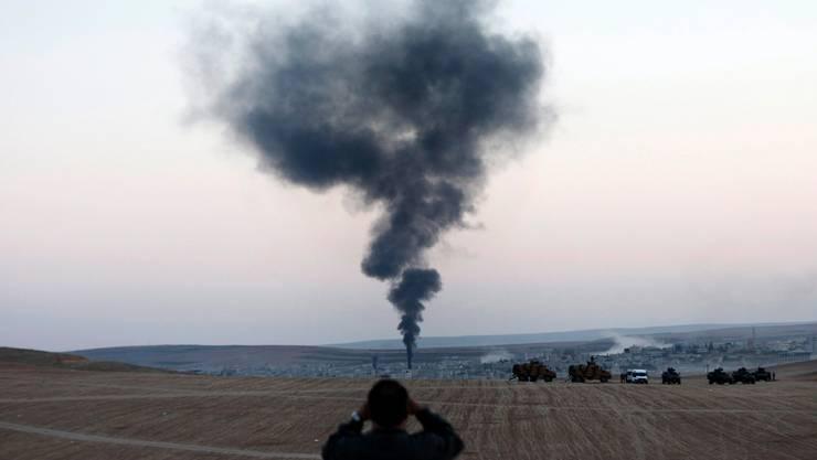 Ein Knall, dann steigt Rauch auf: Blick auf Kobane von der türkischen Grenze aus. SEDAT SUNA/keystone