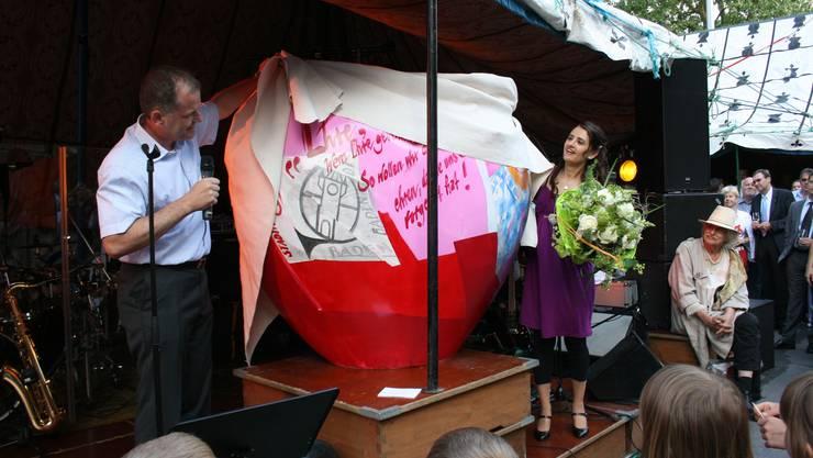 Stephan Attiger enthüllt mit SuzAna Senn-Benes das letzte Herz. Im Hintergrund dessen Gestalter Attila Herendi (mit Hut). (fah)