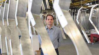CEO André Seiler zwischen Seilbahn-Gondelspanten, die zum Beschichten aufgehängt sind (oben). Spezialitäten der Stebler Blech AG sind unter anderem die Aluminium-Spreizkolben (links) und Auto-Kontrollschilder.
