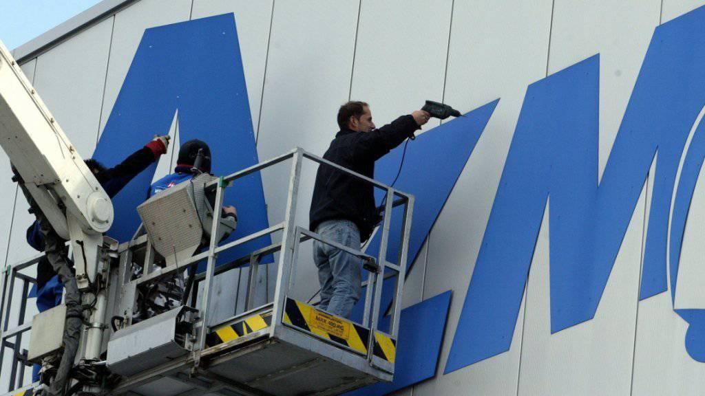 Arbeiter entfernen im März 2006 anlässlich der offiziellen Stabsübergabe der AZM an Emmi den Schriftzug AZM an der Fassade der Aargauer Zentralmolkerei in Suhr. (Archivbild)