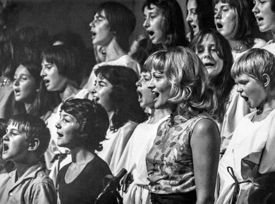"""Ines Torelli singt während der Aufführung """"Schlacht in St. Irgendwo"""" mit Jugendlichen und Kindern. Undatierte Aufnahme."""