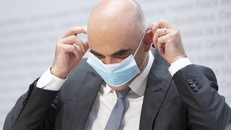 Bundesrat Alain Berset, zieht sich die Schutzmaske an. Während der Medienkonferenz vom vergangenen Freitag hat er die wöchentliche Verdopplung der Infektionen vorausgesagt.