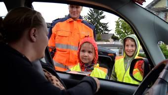 Sarina Balmer und Ray Ineichen zusammen mit Regionalpolizist Markus Baumgartner im kurzen Gespräch mit einer Automobilistin.