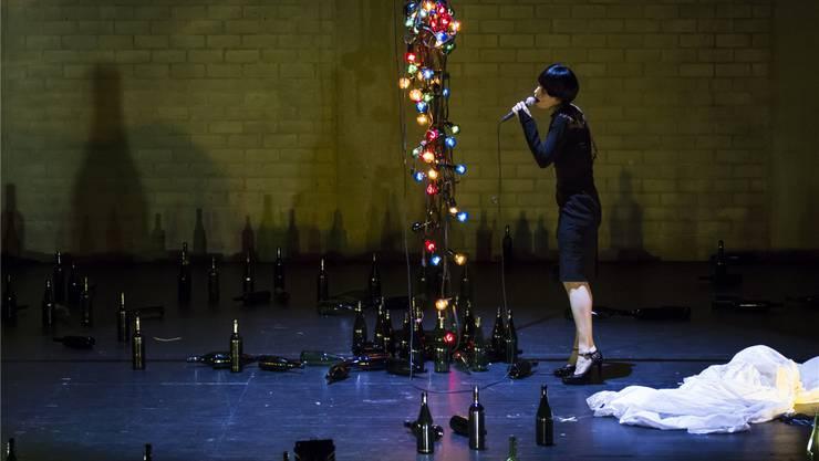 Ruth Rosenfeld singt zur Lampeninstallation, die sich wie von schicksalhafter Geisterhand bewegt auf und ab senkt. Kim Culetto