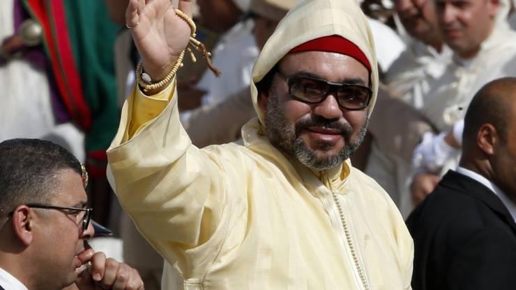 ARCHIV - König Mohammed VI. von Marokko steht bei einer Treue-Zeremonie im Königspalast in Tetouan in einer Limousine und winkt. Marokkos König Mohammed VI. hat sich einem Eingriff am Herzen unterzogen. Foto: Abdeljalil Bounhar/AP/dpa