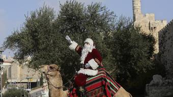 Ein Mann in einem Weihnachtsmann-Kostüm sitzt auf einem Kamel außerhalb der Altstadt von Jerusalem. Foto: Mahmoud Illean/AP/dpa
