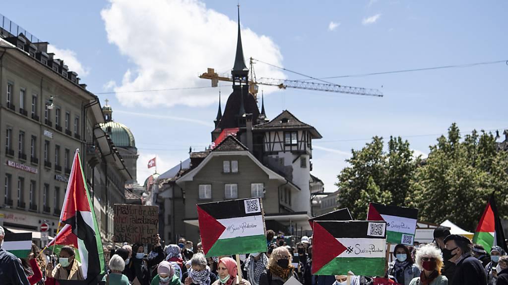 Personen protestieren am Samstag in Bern bei einer Kundgebung gegen die Unruhen in Nahost und plädieren für Frieden in Palästina.