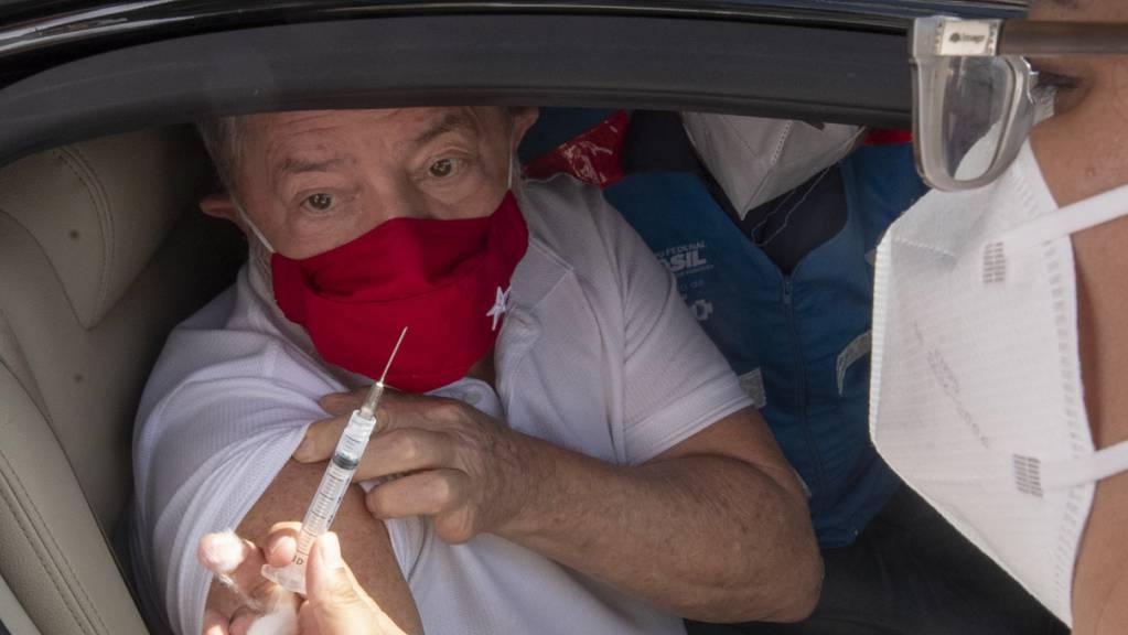 Luiz Inacio Lula da Silva, ehemaliger Präsident von Brasilien, krempelt sich den Ärmel hoch, um an einem Impf-Drive-Thru mit dem Coronaimpfstoff des chinesischen Unternehmens Sinovac geimpft zu werden. Foto: Andre Penner/AP/dpa