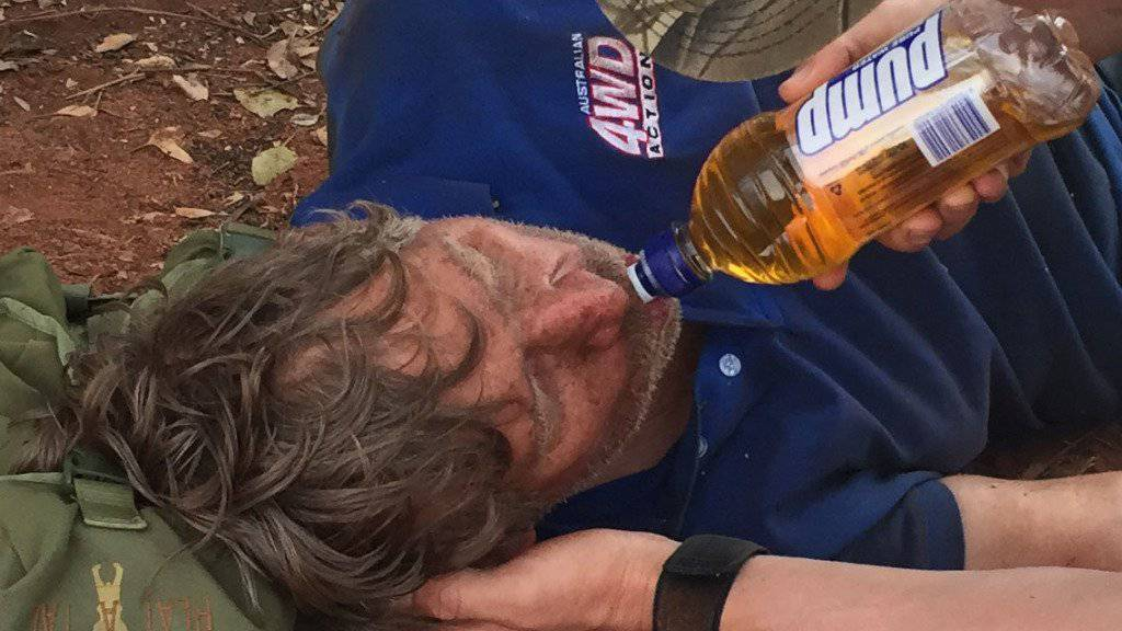Nach Tagen im australischen Busch wird ein Australier völlig dehydriert gerettet. Ein Retter gibt dem 62-Jährigen zu Trinken.