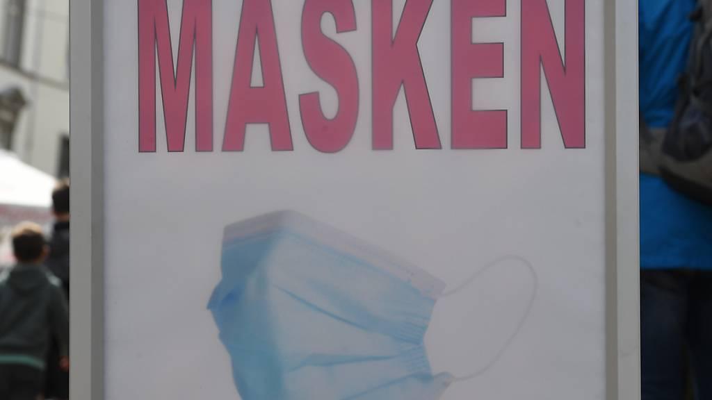 «Masken» steht auf einem Schild in einem Geschäft in der Innenstadt von Stralsund. Die WHO empfiehlt das Tragen von Masken für Kinder ab zwölf Jahren.