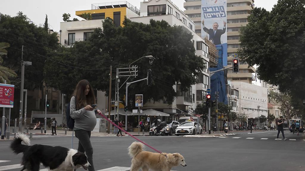 ARCHIV - Eine Passantin geht mit Hunden an einer Gebäudewand in Tel Aviv vorbei. Foto: Sebastian Scheiner/AP/dpa