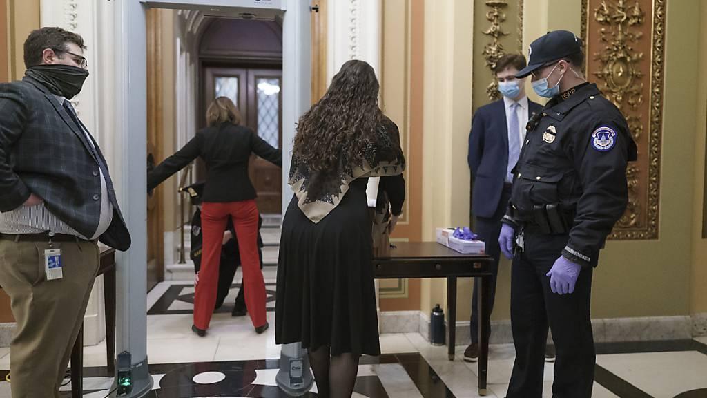 Kongressmitarbeiter gehen durch einen Metalldetektor und Sicherheitskontrolle, bevor sie die Kammer des Repräsentantenhauses betreten. Foto: J. Scott Applewhite/AP/dpa