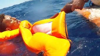 Ein Migrant aus Afrika wird von der italienischen Küstenwache aus dem Mittelmeer gerettet. (Archivbild)