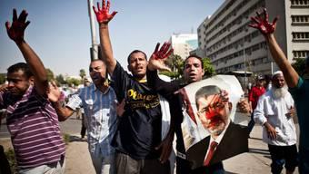 Mursi-Anhänger sind blutverschmiert, nachdem die Polizei angeblich auf die Demonstranten gefeuert hat.