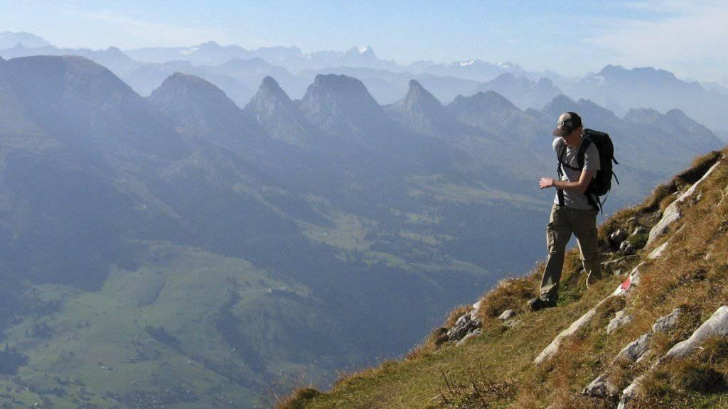 Ein Berggaenger am Freitag, 25. Oktober 2006 vor dem Panorama der Toggenburger Churfirsten mit Hinterrugg, Schibenstoll, Zuestoll, Brisi, Fruemsel und Selun sowie den dahinterliegenden Glarneralpen. (KEYSTONE/Arno Balzarini)